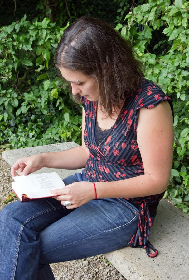 Jonge vrouwenlezing op een bank stock fotografie