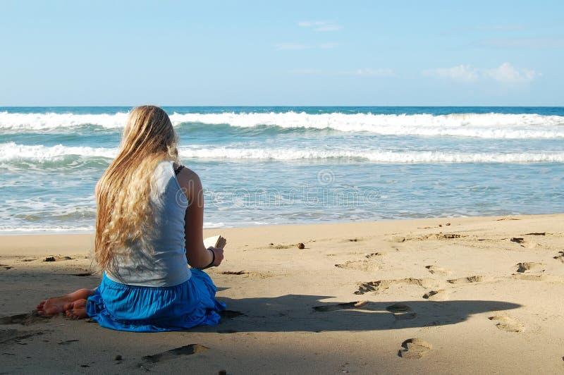 Jonge vrouwenlezing op strand royalty-vrije stock afbeeldingen