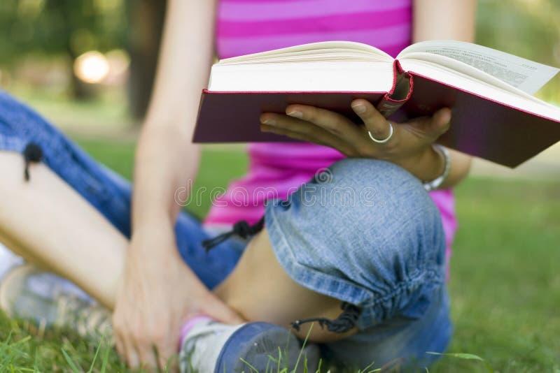 Jonge vrouwenlezing openlucht royalty-vrije stock afbeeldingen