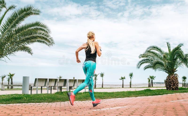Jonge vrouwenlooppas op de overzeese dijk Actieve levensstijl stock foto's