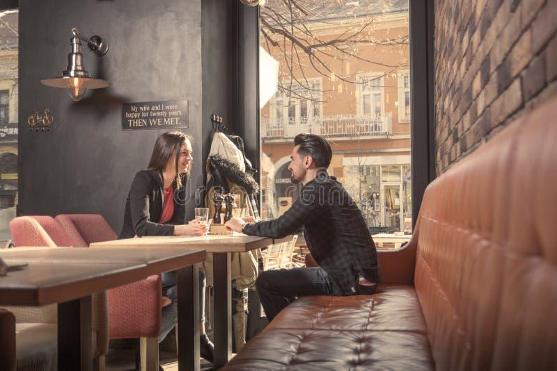 Jonge vrouwenman paarvrienden, het zitten de winkel van de lijstkoffie, het spreken stock afbeelding