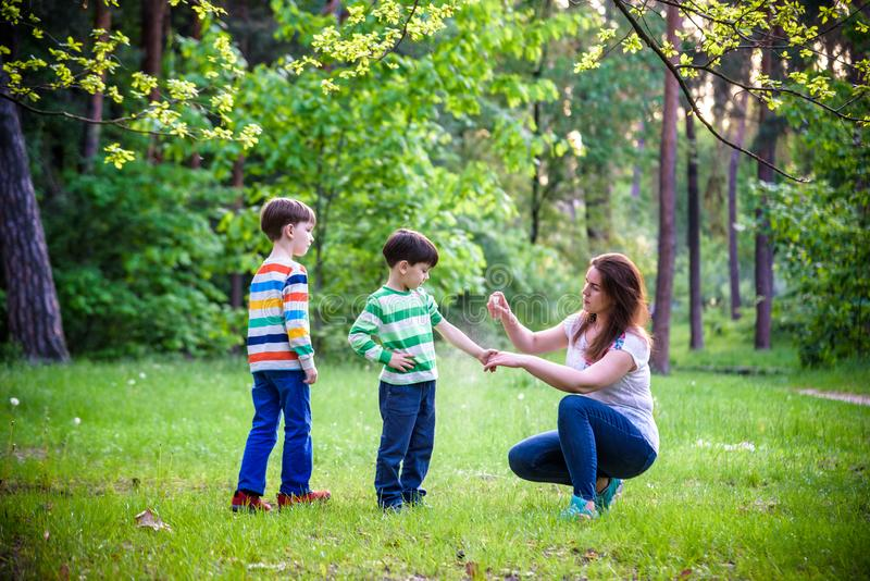 Jonge vrouwenmoeder die insektenwerend middel toepassen op haar zoon twee vóór het bos de stijgings mooie zomer dag of gelijk mak royalty-vrije stock afbeelding