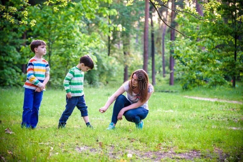 Jonge vrouwenmoeder die insektenwerend middel toepassen op haar zoon twee vóór het bos de stijgings mooie zomer dag of gelijk mak royalty-vrije stock foto's