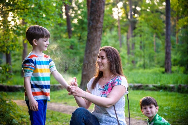 Jonge vrouwenmoeder die insektenwerend middel toepassen op haar zoon twee vóór het bos de stijgings mooie zomer dag of gelijk mak stock afbeelding