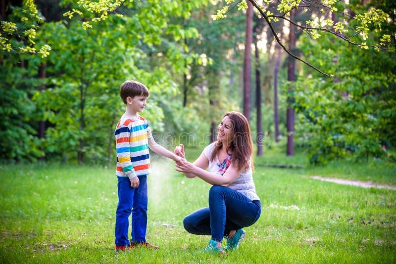 Jonge vrouwenmoeder die insektenwerend middel toepassen op haar zoon vóór het bos de stijgings mooie zomer dag of gelijk maken He royalty-vrije stock fotografie