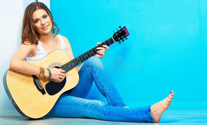Jonge vrouwenmusicus met gitaarzitting op een vloer royalty-vrije stock afbeeldingen