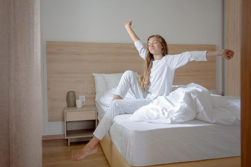 Jonge vrouwenontwaken in haar slaapkamer, die op de bed het uitrekken zich wapens zitten royalty-vrije stock afbeelding