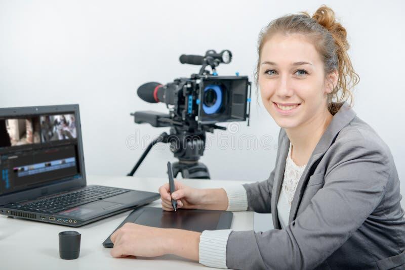 Jonge vrouwenontwerper die grafiektablet voor het video uitgeven gebruiken stock afbeeldingen