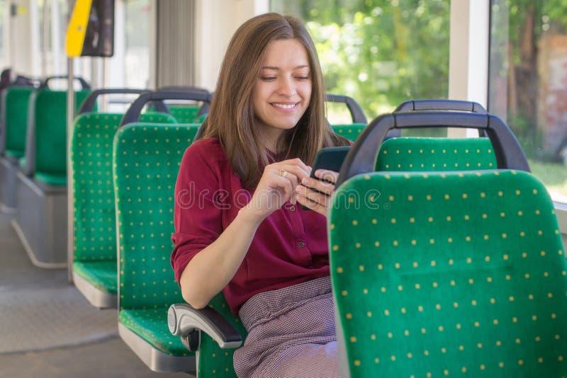Jonge vrouwenpassagier die zich met smartphone bevinden terwijl zich het bewegen in de moderne tram stock foto