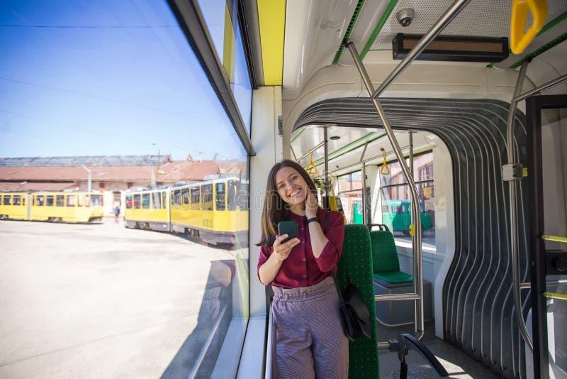 Jonge vrouwenpassagier die zich met smartphone bevinden terwijl zich het bewegen in de moderne tram stock fotografie