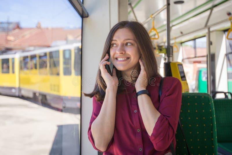 Jonge vrouwenpassagier die zich met smartphone bevinden terwijl zich het bewegen in de moderne tram royalty-vrije stock afbeeldingen