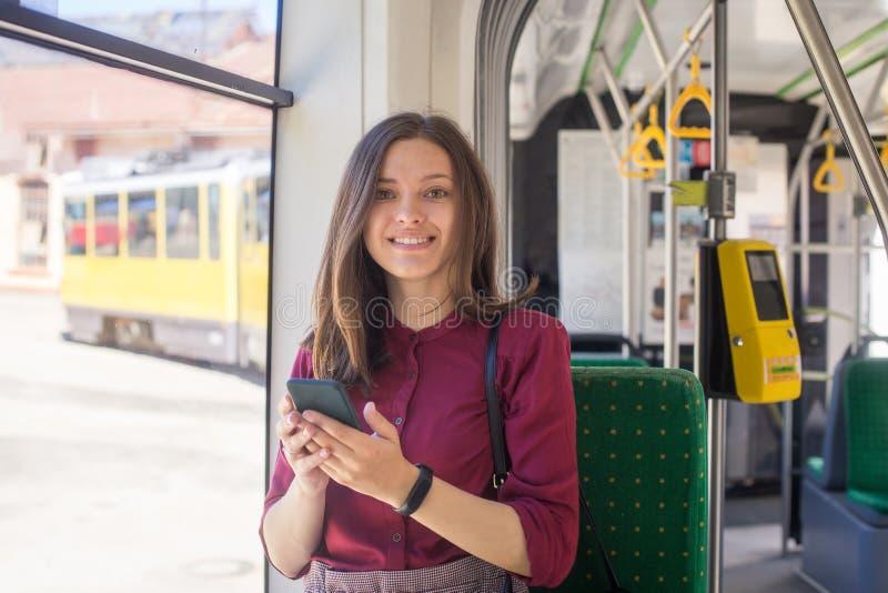 Jonge vrouwenpassagier die zich met smartphone bevinden terwijl zich het bewegen in de moderne tram stock afbeeldingen