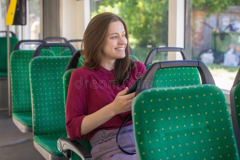 Jonge vrouwenpassagier die zich met smartphone bevinden terwijl zich het bewegen in de moderne tram royalty-vrije stock foto's