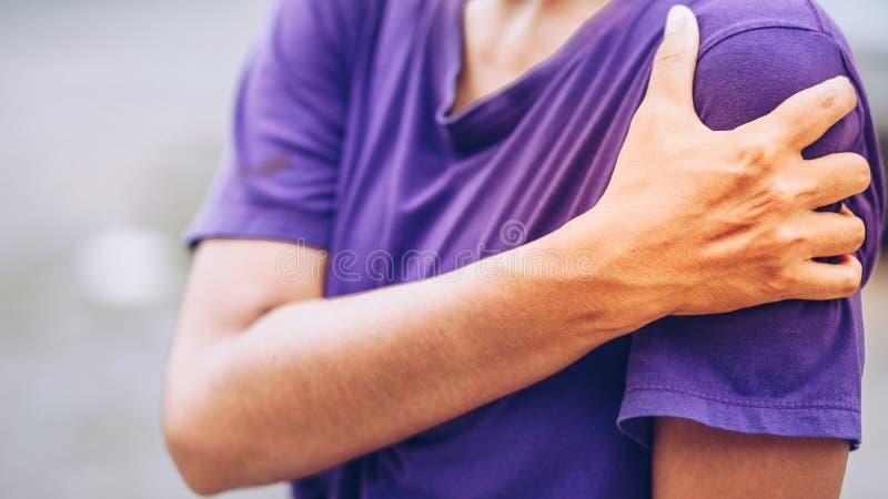 Jonge vrouwenpijn verlaten schouder stock fotografie