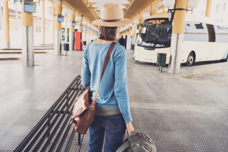 Jonge vrouwenreiziger die op een bus op een busstation, een reis en een actief levensstijlconcept wachten stock foto's