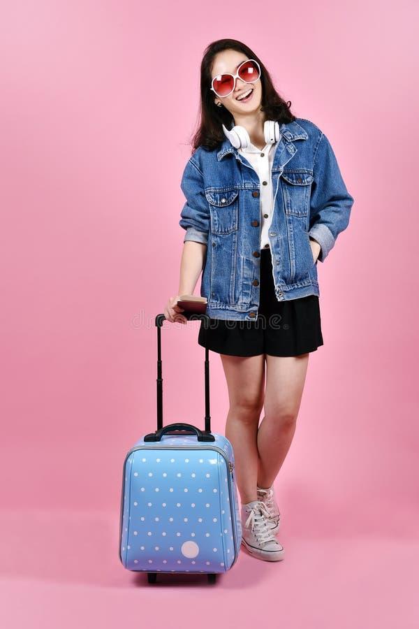 Jonge vrouwenreiziger die roze koffer en paspoortdocument over roze achtergrond houden stock afbeeldingen