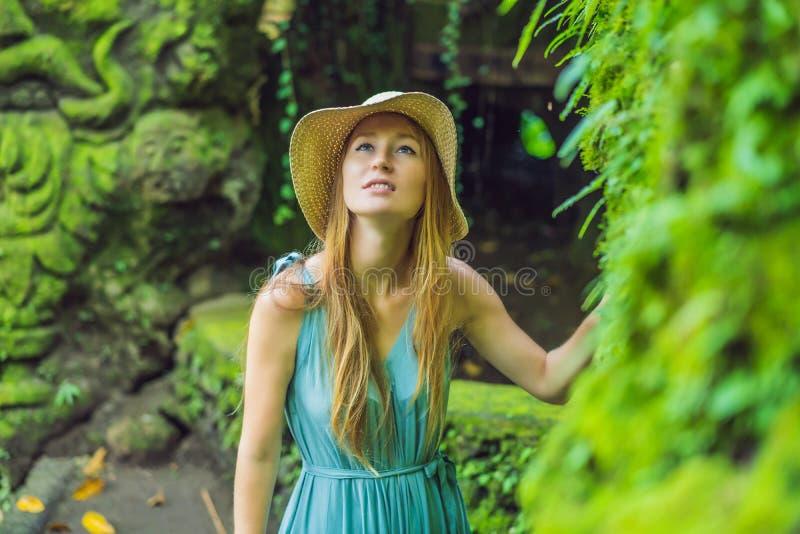Jonge vrouwenreiziger in een Balinese die tuin met mos wordt overwoekerd Reis naar het concept van Bali royalty-vrije stock foto