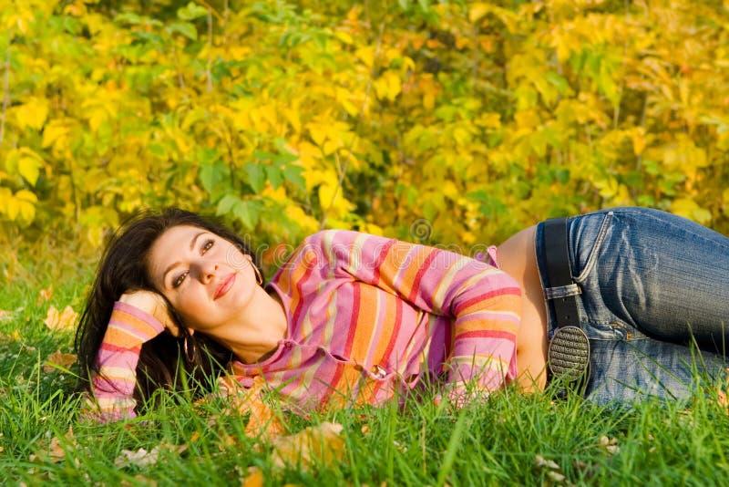 Jonge vrouwenrust op het de herfstgras stock foto