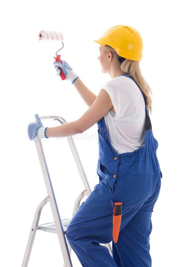 Jonge vrouwenschilder in blauwe bouwer eenvormige status op ladder w stock afbeelding