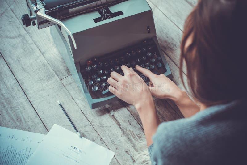Jonge vrouwenschrijver in bibliotheek thuis creatieve beroep het typen schrijfmachine royalty-vrije stock afbeelding