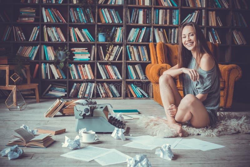 Jonge vrouwenschrijver in bibliotheek thuis het creatieve beroep lachen royalty-vrije stock afbeelding