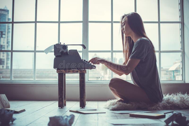 Jonge vrouwenschrijver in bibliotheek thuis het creatieve beroep typen dichtbij venster stock foto