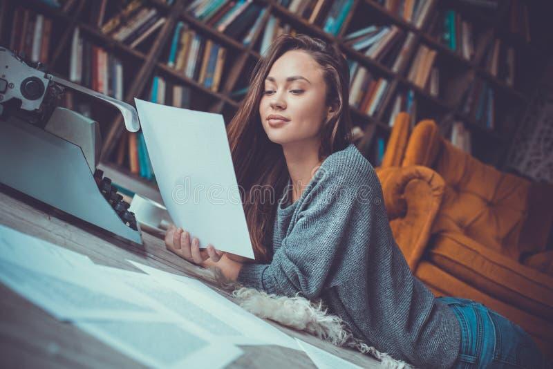 Jonge vrouwenschrijver in de lezingspagina van het bibliotheek thuis creatieve beroep stock afbeelding