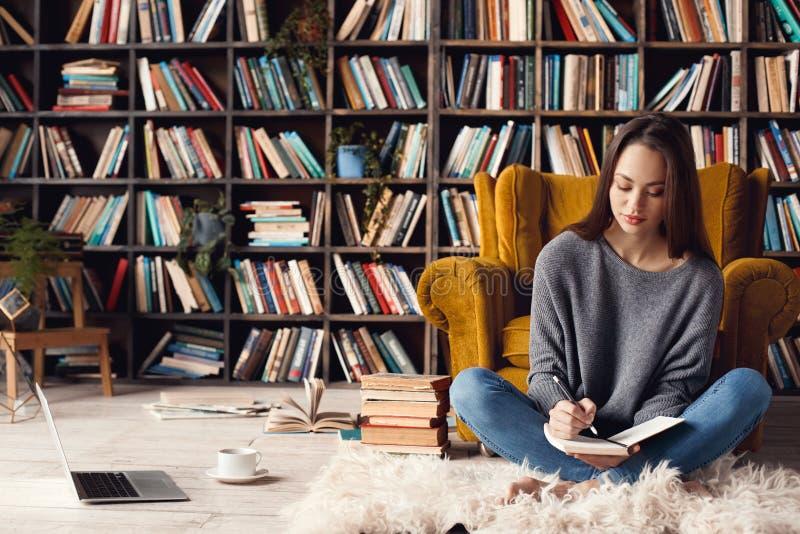 Jonge vrouwenschrijver in de zitting van het bibliotheek thuis creatieve beroep het schrijven nota's stock foto's