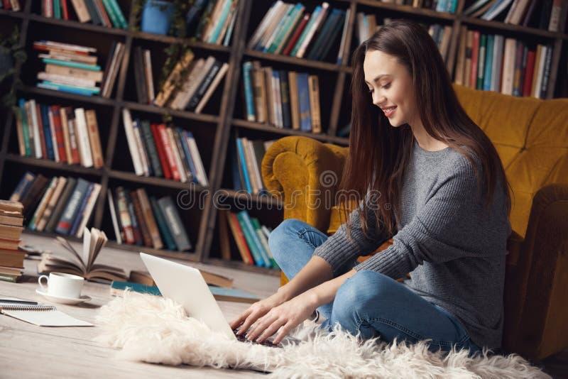 Jonge vrouwenschrijver in de zitting van het bibliotheek thuis het creatieve beroep typen op laptop stock foto's