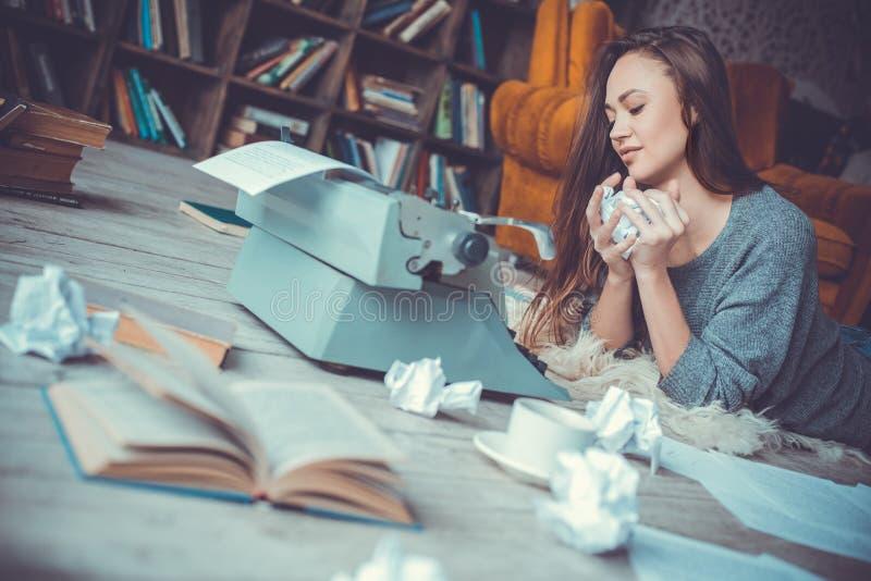 Jonge vrouwenschrijver die in bibliotheek thuis creatief beroep document close-up verfrommelen stock afbeelding