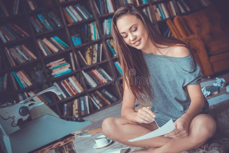 Jonge vrouwenschrijver die in bibliotheek thuis creatief beroep grammatica controleren stock afbeelding