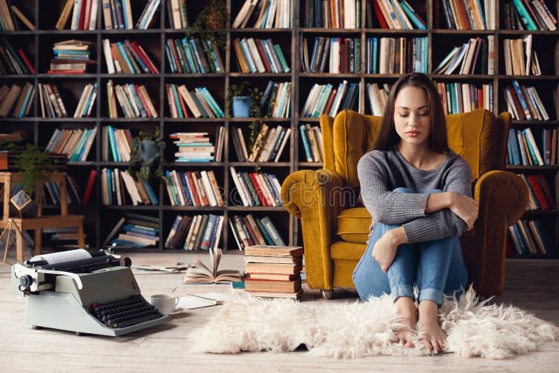 Jonge vrouwenschrijver in verstoorde zitting van het bibliotheek de thuis creatieve beroep stock foto