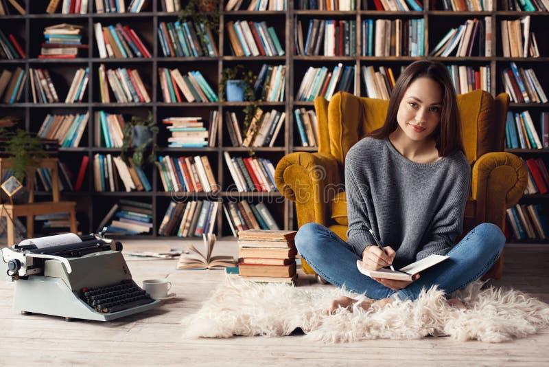 Jonge vrouwenschrijver in zitting die van het bibliotheek de thuis creatieve beroep nota's nemen royalty-vrije stock fotografie