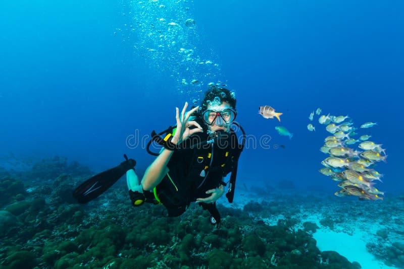Jonge vrouwenscuba-duiker die O.K. gebaar tonen stock afbeelding