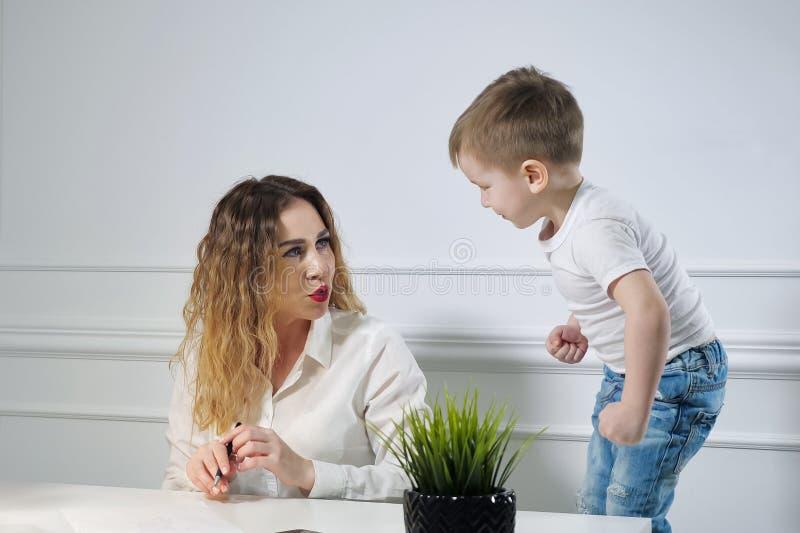 Jonge vrouwensecretaresse met haar weinig zoon in de werkplaats in bureau Werkende moeder stock foto