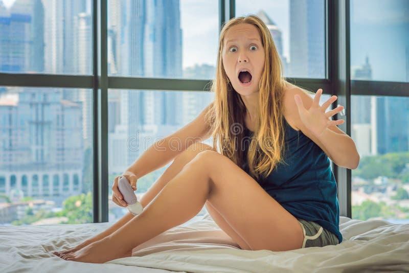Jonge vrouwensitin op bed thuis en doend epilation met epilator op benen en is in pijn Op de achtergrond van een vensteroverlooki stock foto