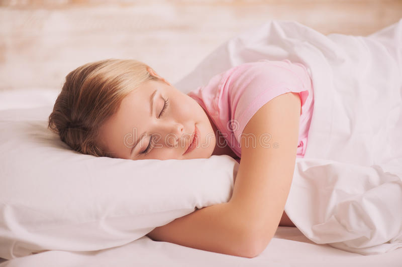 Jonge vrouwenslaap in bed royalty-vrije stock afbeelding