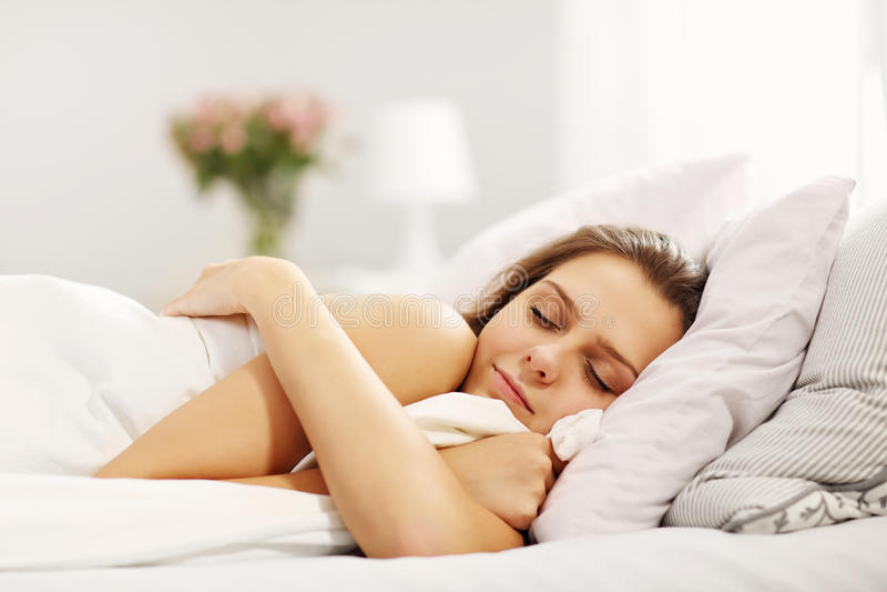 Jonge vrouwenslaap in bed royalty-vrije stock foto's
