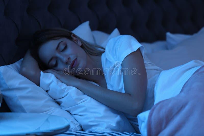 Jonge vrouwenslaap in bed bij nacht stock foto's