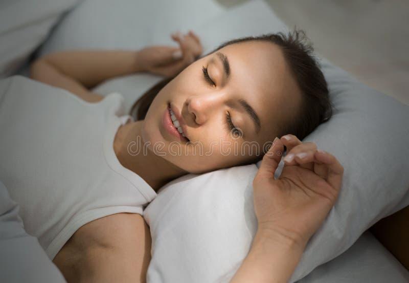 Jonge Vrouwenslaap in Bed comfortabel en gelukzalig royalty-vrije stock foto