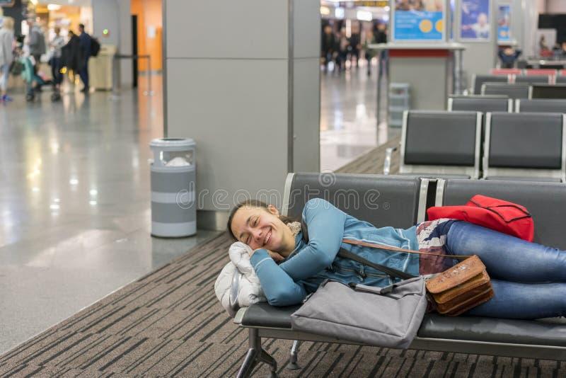 Jonge vrouwenslaap bij de luchthaven terwijl het wachten op haar vlucht Vermoeide vrouwelijke reizigersslaap op de poorten van he royalty-vrije stock afbeelding