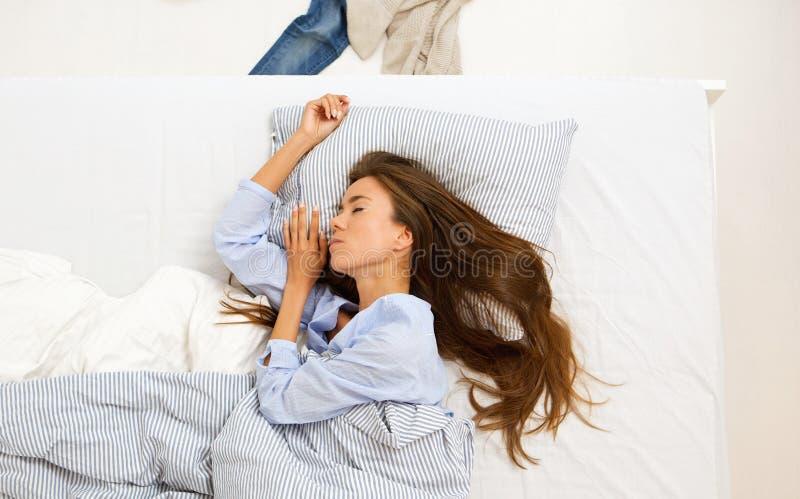 Jonge vrouwenslaap in comfortabel bed royalty-vrije stock fotografie