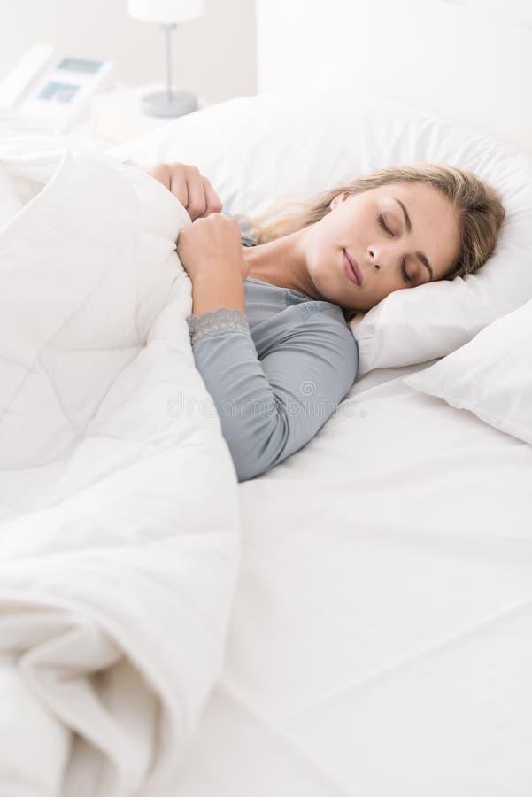 Jonge vrouwenslaap in de slaapkamer stock afbeeldingen