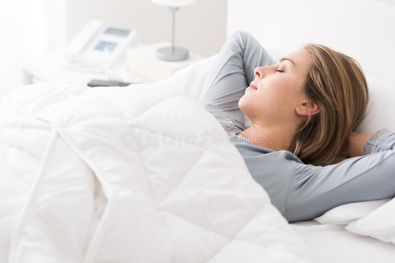 Jonge vrouwenslaap in de slaapkamer royalty-vrije stock afbeelding