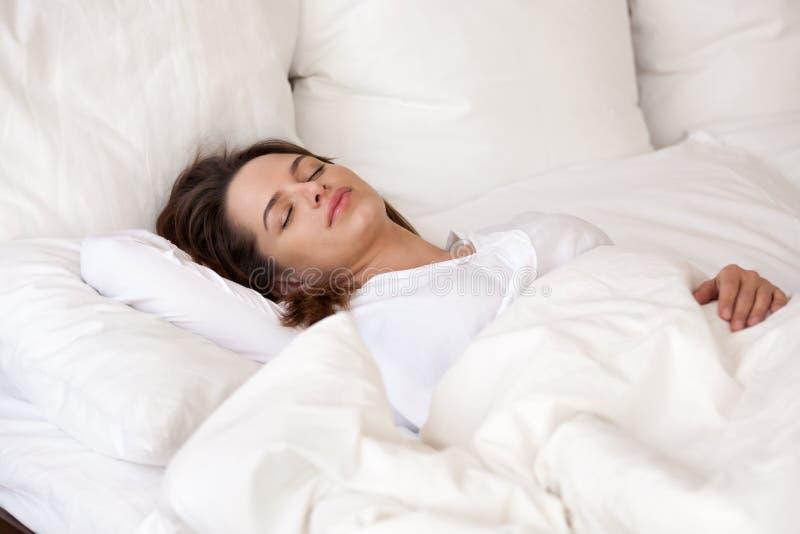 Jonge vrouwenslaap goed in comfortabel bed met wit linnen stock foto's