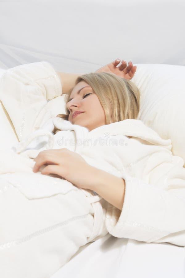 Jonge vrouwenslaap met uitgestrekte handen stock afbeelding
