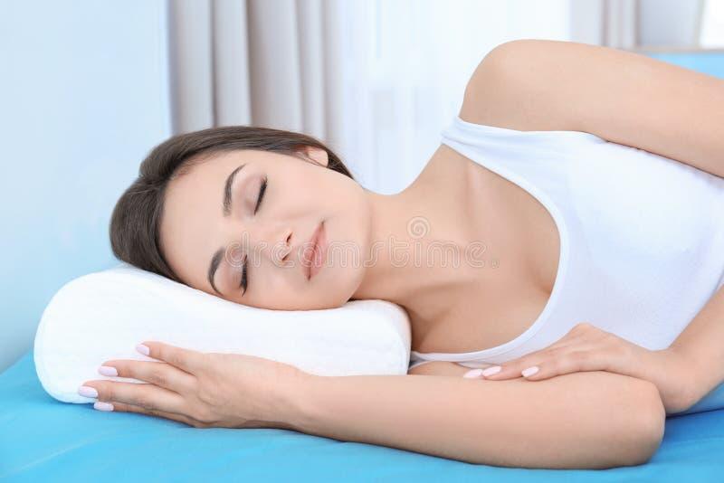 Jonge vrouwenslaap op bed met orthopedisch hoofdkussen royalty-vrije stock foto's