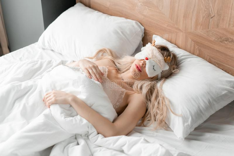 Jonge vrouwenslaap op comfortabel bed in een masker voor slaap Blinddoek op oog Ochtend in hotelruimte Wit hoofdkussen en stock fotografie