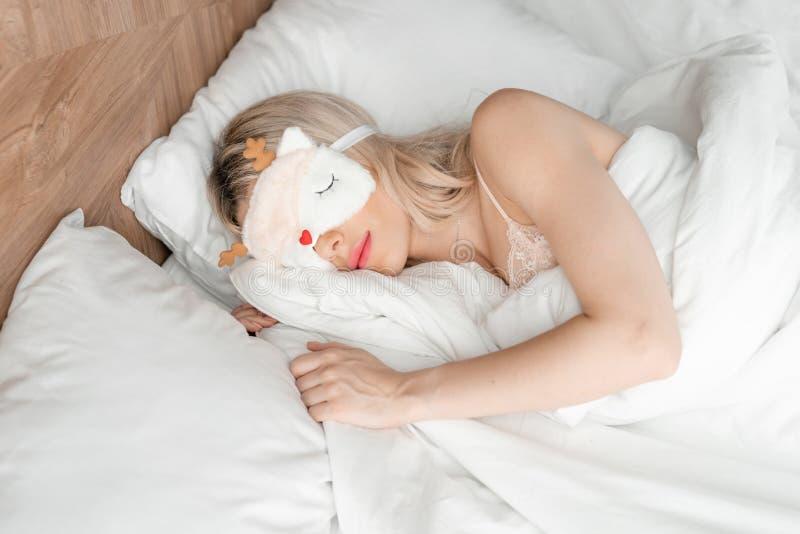 Jonge vrouwenslaap op comfortabel bed in een masker voor slaap Blinddoek op oog Ochtend in hotelruimte Wit hoofdkussen en royalty-vrije stock foto
