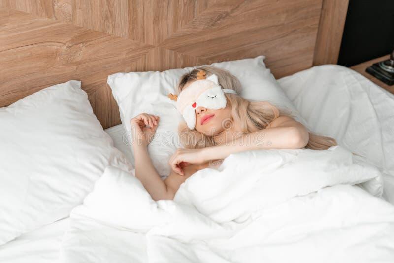 Jonge vrouwenslaap op comfortabel bed in een masker voor slaap Blinddoek op oog Ochtend in hotelruimte Wit hoofdkussen en stock afbeelding